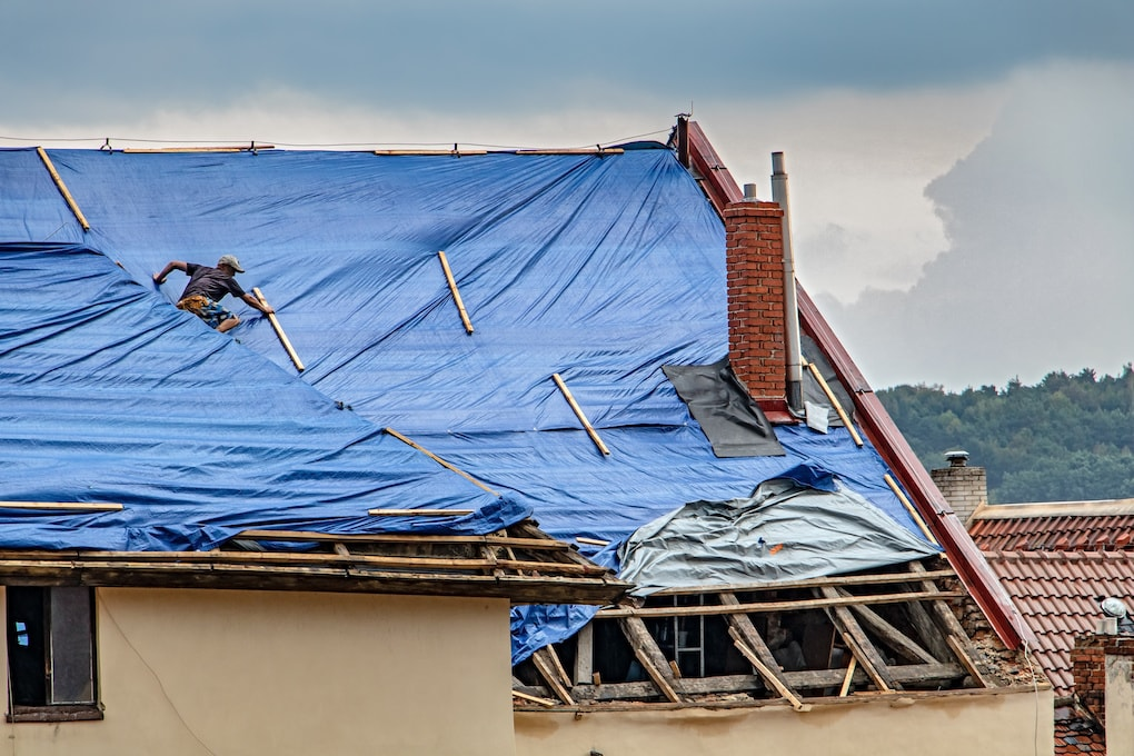 roofer placing tarp on roof